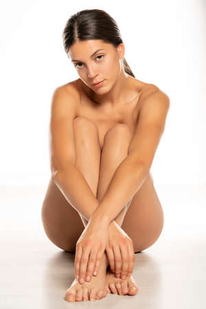 young seductive naked woman sitting on white floor