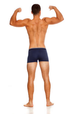 Back view of shirtless handsome man in panties on white background showing his biceps