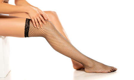 Woman wearing black fish net nylon socks on white background Standard-Bild