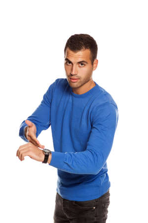 handsome young man in blouse pointing on his wrist watch  on white background