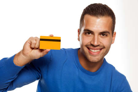 portrait of happy young man, holding empty credit card on white background Standard-Bild