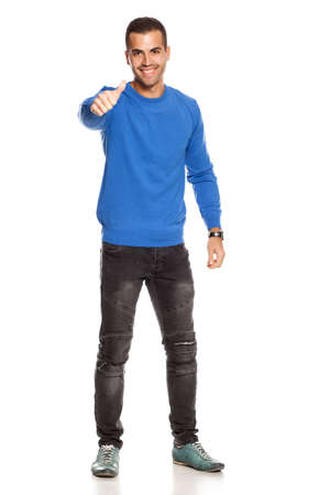 handsome happy young man in blouse and jeans  on white background showing thumbs up