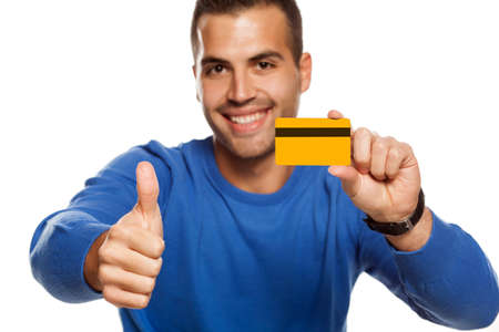 portrait of happy young man, holding empty credit card on white background and showing thumbs up