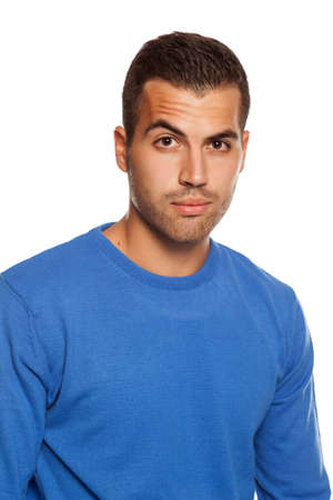 young man in blouse with skeptical look on white background