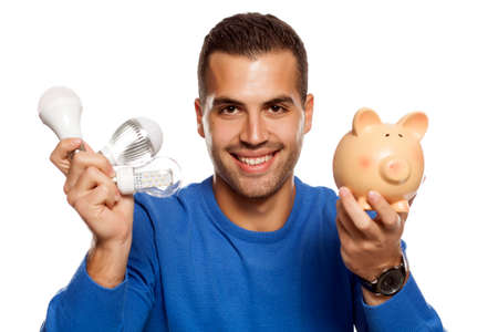 portrait of happy young man, holding three different LED bulbs and piggy bank on white background