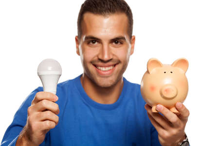 portrait of happy young man, holding LED bulb and piggy bank on white background Stok Fotoğraf