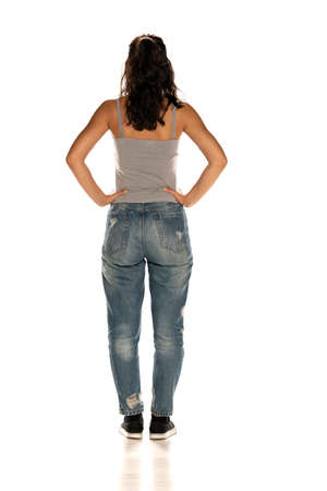 Back view of young dark skinned woman in jeans standing on white background Stok Fotoğraf