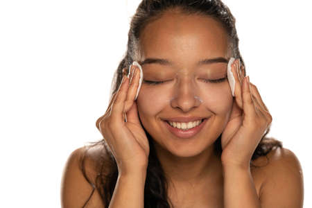 Young dark skinned woman cleaning her face with cotton pads on white background