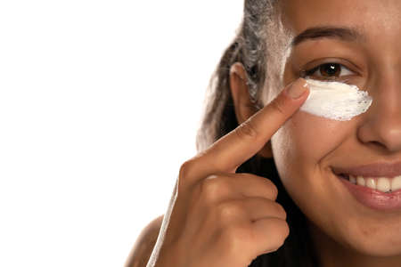 Young  dark skinned woman applying a creme on her  low eyelids on white background