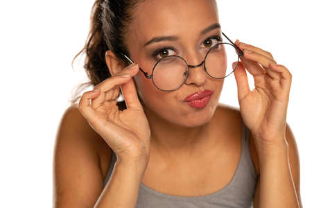 Happy young dark skinned woman with eyeglasses on white background