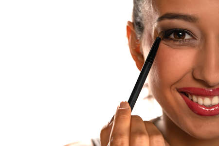 Young dark skinned woman applying eyeshadow on white background