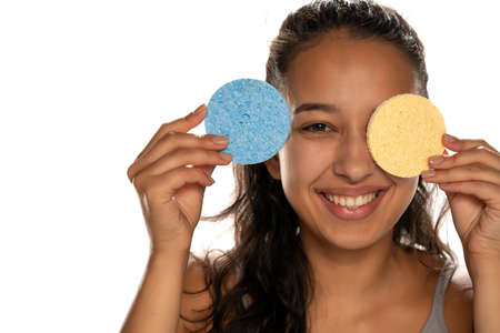 Young dark skinned woman cleaning her face with sponge pads on white background