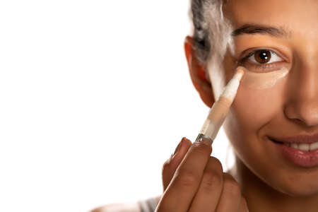 Young dark skinned woman applying concealer on her low eyelids on white background