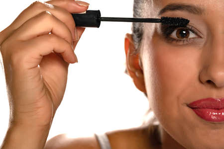 Young dark skinned woman applying a mascara on white background Stok Fotoğraf