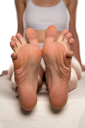 Young woman relaxing her feet with stretching toes on white background Stok Fotoğraf