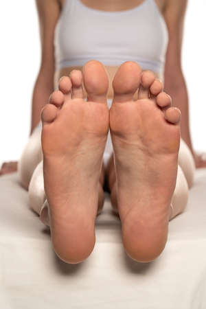 Young woman relaxing her feet on white background