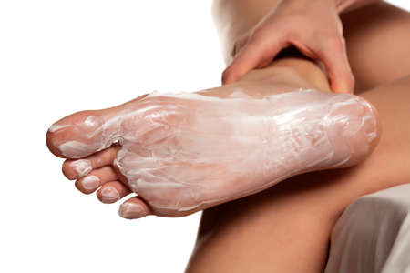 Female foot with foot mask on white background