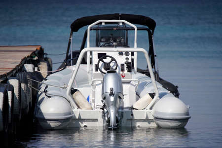 inflatable boat with a powerful engine tied to the dock
