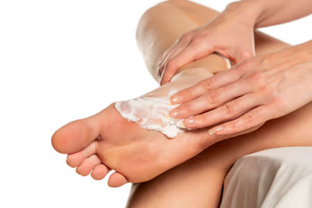 Woman applying foot mask on her sole feet on white background