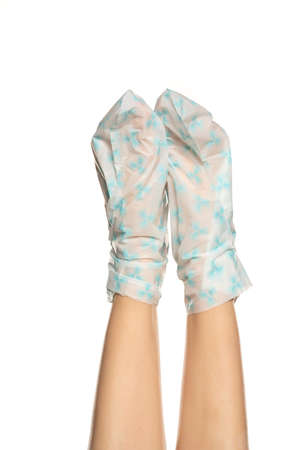 Female feet wrapped with plastic bags with foot mask on white background Stok Fotoğraf