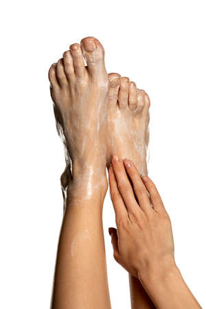 Woman applying foot cream on her bare feet on white background Stok Fotoğraf