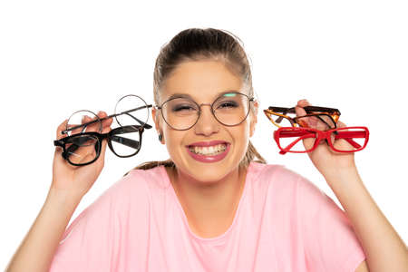 a young woman chooses a frame for her new glasses on white background Stockfoto