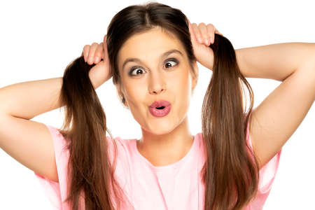 Young funny woman with ponny tails make a faces on white background