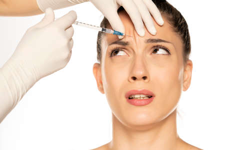 Portrait of a young scared woman on a faace filler injection procedure on white background