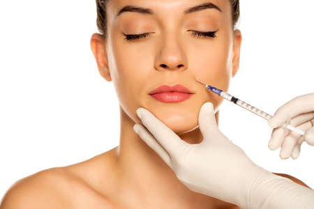Portrait of a young beautiful woman on a face filler injection procedure on white background