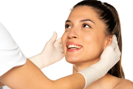 doctor's hands in gloves checks a face of young happy woman on white background