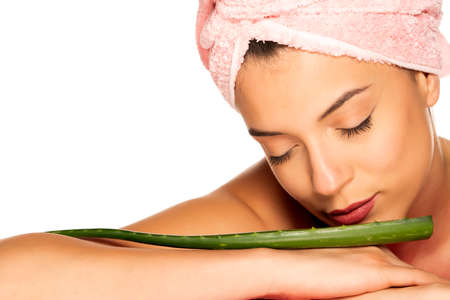 Young shirtless woman posing with a leaf of aloe vera on white background