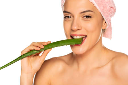 Young shirtless woman biting a leaf of aloe vera on white background