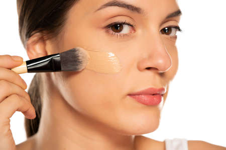 Young woman applying liquid foundation with the brush on her face