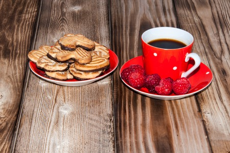 Ripe raspberry and coffee cup on the old wooden table top