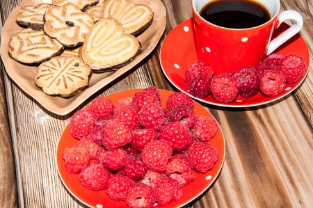 Ripe raspberry coffee cup and cookies on the old wooden table top Stock Photo