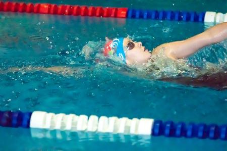 ORENBURG, ORENBURG region, RUSSIA, 21 November, 2014 year. Outdoor city tournament on swimming Autumn starts in the city of Orenburg administration prizes. Girl backstroke