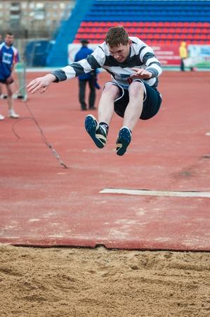 institutions: Orenburg, Russia - 24 April 2015: Men compete in long jump on the sports contest students of institutions of secondary vocational education Youth of the Orenburga Editorial