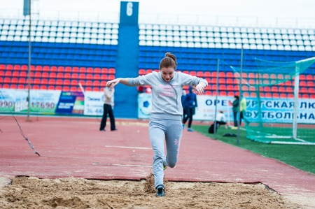 secondary education: Orenburg, Russia - 24 April 2015: Girl performs a long jump on the sports contest students of institutions of secondary vocational education Youth of the Orenburga