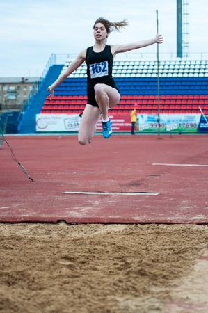 institutions: Orenburg, Russia - 24 April 2015: Girl performs a long jump on the sports contest students of institutions of secondary vocational education Youth of the Orenburga