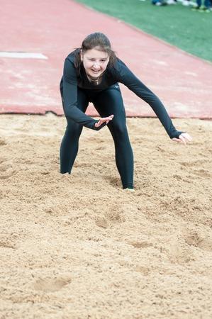 """salto de longitud: Orenburg, Rusia - 24 de abril 2015: La muchacha lleva a cabo un salto de longitud en los estudiantes del concurso deportes de las instituciones de educación profesional de nivel secundario """"Juventud del Orenburga"""""""