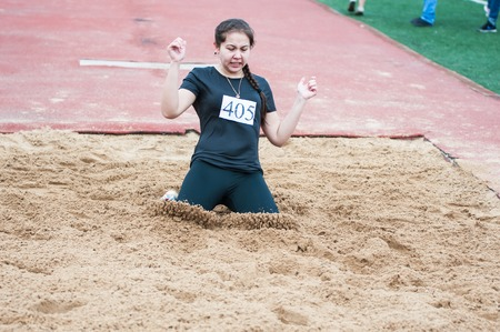 vocational: Orenburg, Russia - 24 April 2015: Girl performs a long jump on the sports contest students of institutions of secondary vocational education Youth of the Orenburga