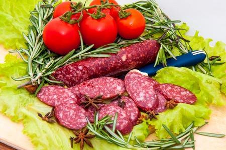 plato del buen comer: Slice sausage and Fresh Greens on a wooden countertop