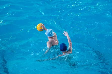 water polo: Los niños están jugando waterpolo en la piscina cubierta