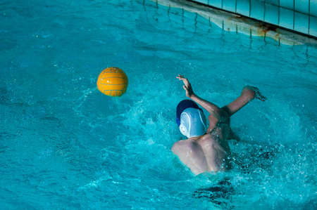 waterpolo: The boys are playing water polo in the indoor swimming pool