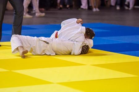 compete: Two girls judoka in kimono compete on the tatami