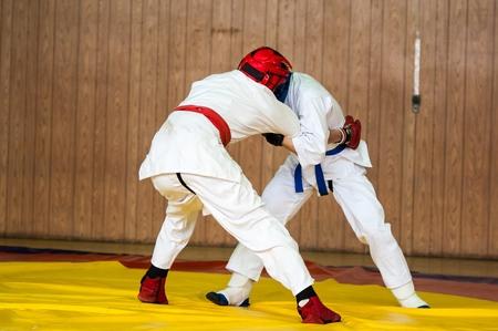 Niños combatientes compiten en deportes de combate cuerpo a cuerpo Foto de archivo