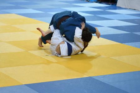 Two Girls judoka in kimono compete on the tatami Stok Fotoğraf