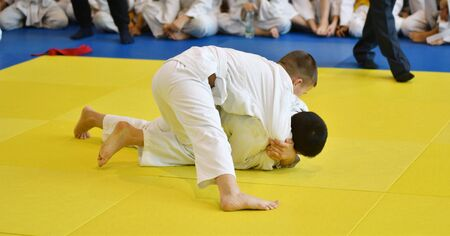 Two Boys judoka in kimono compete on the tatami