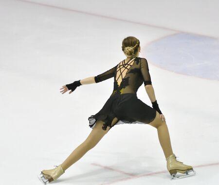 Girl skater skates on ice sports arena 写真素材