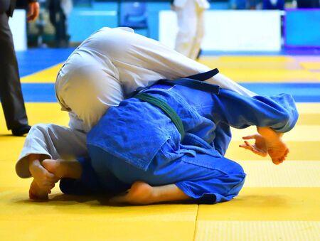 Two Girls judoka in kimono compete on the tatami